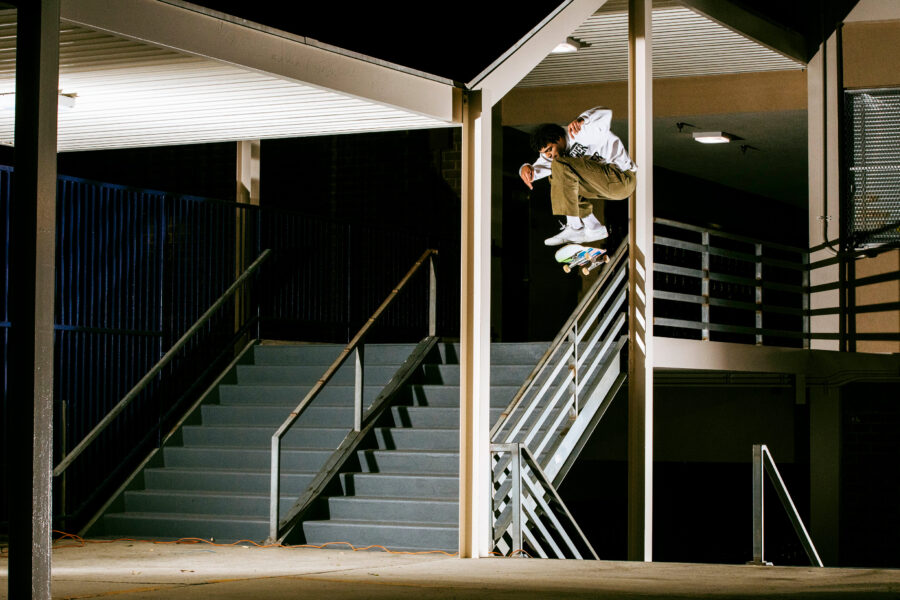 Justin Henry nollie kickflips over a handrail whilst weaving between two bars. Photo by Dakota Mullins.