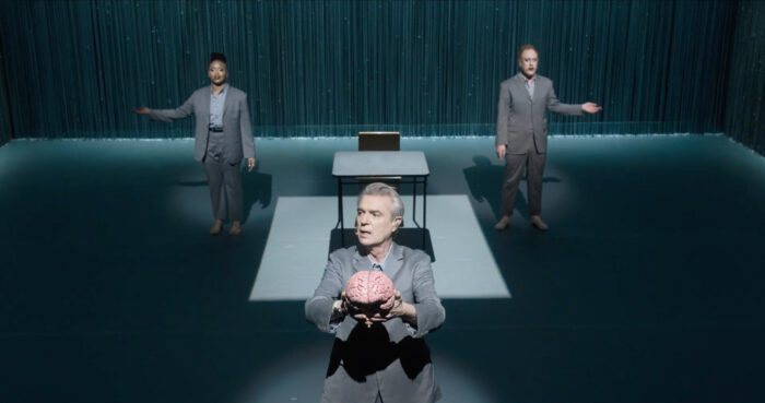 David Byrne holding a plastic brain in a still from the Broadway performance film of 'American Utopia', directed by Spike Lee (2020) | Offerings: Tom Karangelov Intrerview